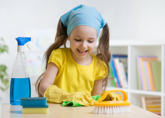 Little child girl cleaning her nursery room. Kid wiping table with yellow rag and holds spray on table.