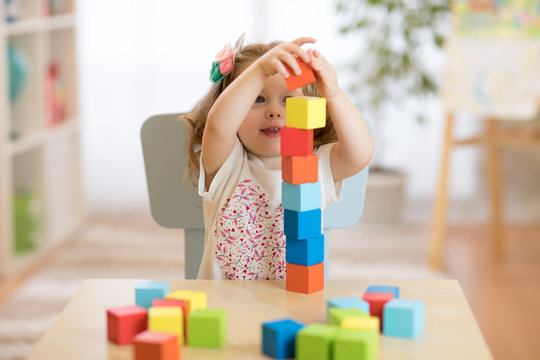 Kid girl playing with block toys in daycare center