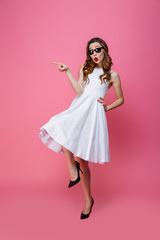 Photo of cute excited woman in dress and sunglasses pointing finger aside on copyspace, isolated over pink background