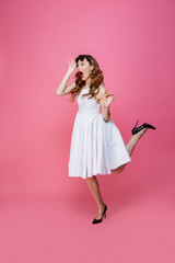 Adorable caucasian woman in white dress taking off sunglasses and looking aside on copyspace with surprise, isolated over pink background