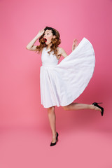 Fascinating young woman with flowing white dress taking off sunglasses and looking aside on copyspace with surprise, isolated over pink background