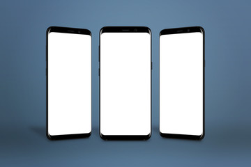 Three modern smartphones with round edges and isolated screen for mockup on blue background.