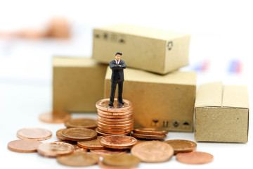 Miniature people : businessman stand on coins,business concept.