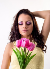 Attractive young brunette woman holding fresh flowers