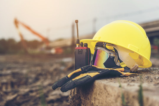 Yellow helmets, gloves, radio communication and safety glasses placed on the cement floor are the background of the construction of blurred buildings.