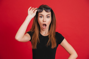 Photo of trendy brunette woman wearing black t-shirt taking off sunglasses and looking on camera with open mouth, isolated over red background