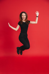 Full-length portrait of positive woman 20s wearing black t-shirt, rejoicing and jumping in air isolated over red background
