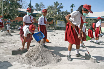 Students clean their school yard from ash after Mount Sinabung volcano erupted on Monday at Payung village in Karo