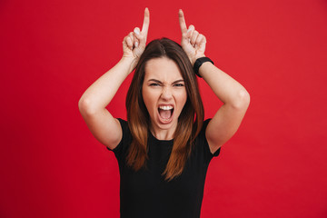 Portrait of crazy woman 20s wearing black screaming and playfully showing horns with two fingers, isolated over red background