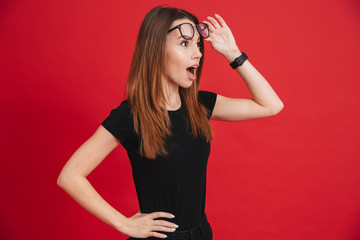 Closeup image of young woman 20s wearing black t-shirt taking off glasses and looking aside in surprise isolated over red background