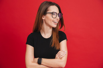 Photo of splendid woman 20s wearing black t-shirt, wristwatch and eyeglasses posing aside with hands folded and wonderful smile isolated over red background