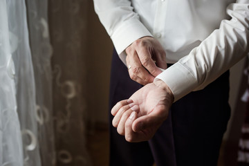 Businessman dresses white shirt, male hands closeup,groom getting ready in the morning before wedding ceremony