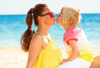 trendy mother and daughter on seashore kissing