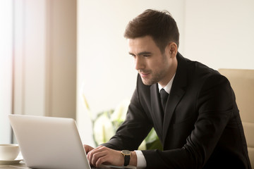 Attractive man in business suit using laptop while sitting at desk. Millennial businessman reading e-mail, surfing in Internet, communicating with colleagues online while working on computer in office