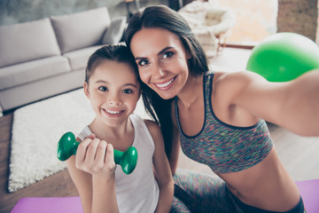 Let's take a picture for social network! Close up portrait of beautiful sportive cute gentle tender mother and daughter wearing sporty clothes making video call via internet connection