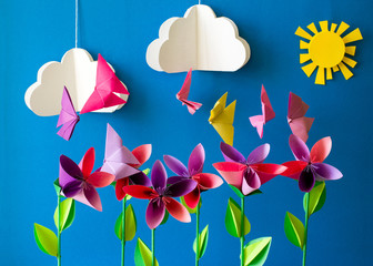 Origami paper flowers, butterflies, clouds and sun. Paper art craft