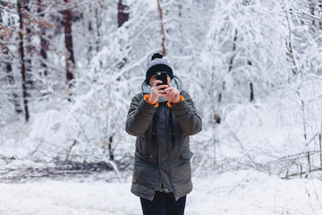 a guy walking along a snow-covered road near a pine forest, taking pictures on the phone and looking at photographs
