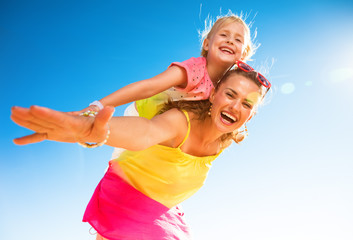 smiling modern mother and daughter on seashore having fun time