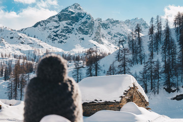 Woman looking the mountain and walking toward old snowy cottage in mountain during the winter season - Blurred Woman's head