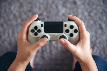 Top view image of hands holding the game controller while playing games