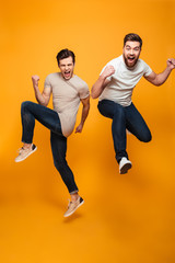 Portrait of a two cheerful young men jumping