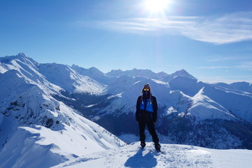Top of Kopa Kondracka with a young man during winter with a view on Kasprowy Wierch, Zakopane, Tatry mountains, Poland
