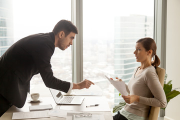Serious company leader strictly insisting on fulfilling terms of contract during negotiators with businesswoman at office. Angry male client requiring satisfaction of claims in confused female manager