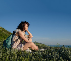 beautiful brunette woman sitting on grass on hill over sea.Travel woman with backpack near ocean. Travel, lifestyle concept