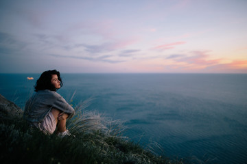 smiling beautiful brunette woman sitting on grass on hill and looking out to sea. girl relaxing outdoor. Travel woman ejoing view of ocean. Traveling, freedom and active lifestyle concept