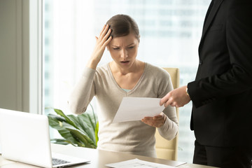 Boss giving dismissal notification to confused female office worker. Millennial woman shocked because of unexpected firing from job. Puzzled businesswoman reading lawsuit text, mistakes in document