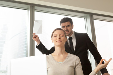 Funny young woman with peaceful facial expression meditating at workplace in office, angry boss with documents in hands arguing and screaming at background. Businesswoman resisting stress at work