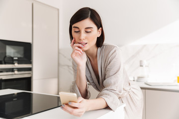 Photo of attractive woman with short dark hair wearing beautiful robe posing in kitchen, and chatting or surching internet on smartphone