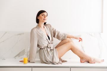 Portrait of sexual slim woman with short dark hair wearing robe posing in kitchen, sitting on table in sunny morning and drinking orange juice