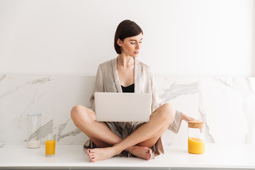 Image of smart brunette woman wearing bathrobe sitting on table in kitchen with legs crossed, and using laptop