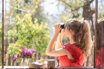 Young girl with vintage red dress watching birds in the morning sun by the window, while tea , cookies , book and lilac flowers are waiting next to her
