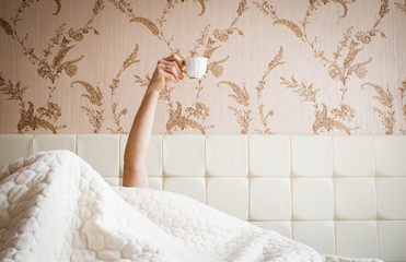 Soft photo of woman on the bed with cup of coffee. Top view