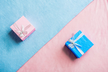 Top view blue and pink beautiful gifts locating opposite each other on fabric. Festive concept
