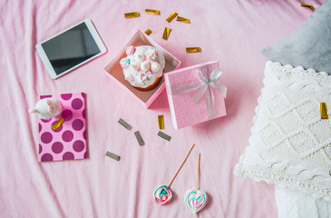Top view gift with delicious Easter cake. Electronic tablet, copybook and sweets locating near it. Leisure concept