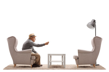 Angry mature man arguing with an empty armchair