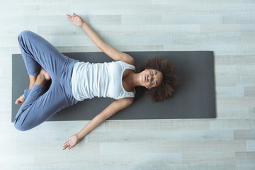 Top view full length serene african female making yoga while lying on floor in room. Copy space