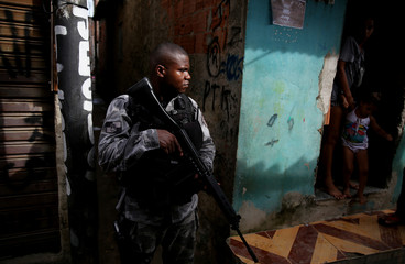 A military police officer patrols the Kelson's slum during a joint operation with the armed forces in Rio de Janeiro