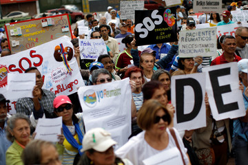 People holding placards and shouting slogans take part in a protest against medicinal shortages in Caracas