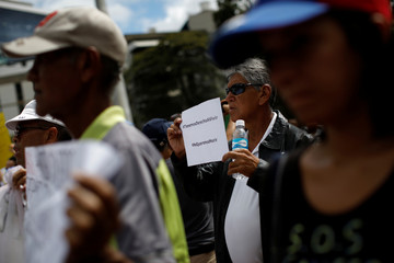 """Guillermo Habanero, 56, a kidney transplanted patient, holds a placard that reads, """"We have the right to live. We do not want to die"""" while he takes part in a protest against medicinal shortages in Caracas"""
