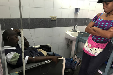 Pablo Tejada, a kidney transplanted patient, receives treatment in front of his daughter at a state hospital in Caracas