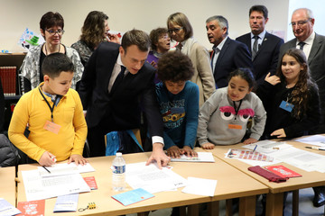 French President Emmanuel Macron and French Culture Minister Francoise Nyssen meet with youths during a visit at a mediatheque in Les Mureaux