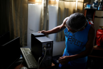 Guillermo Habanero, 56, a kidney transplanted patient, works on the computer of a client at his house in Caracas