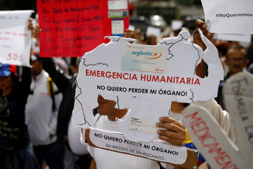 Reinaldo Olivares, a kidney transplanted patient, holds a placard with the shape of the map of Venezuela, during a protest against medicinal shortages in Caracas