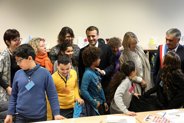 French President Emmanuel Macron visits a mediatheque in Les Mureaux