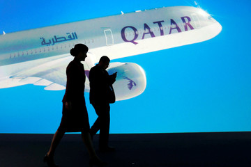 People are silhouetted in front of a screen as Airbus delivers the first A350-1000, the largest member of the new Airbus wide-body family and the largest twin-engined jet built in Europe, to Qatar Airways, in Blagnac near Toulouse