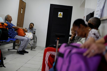 Kidney disease patients and their relatives wait at the waiting room of a dialysis center in Caracas
